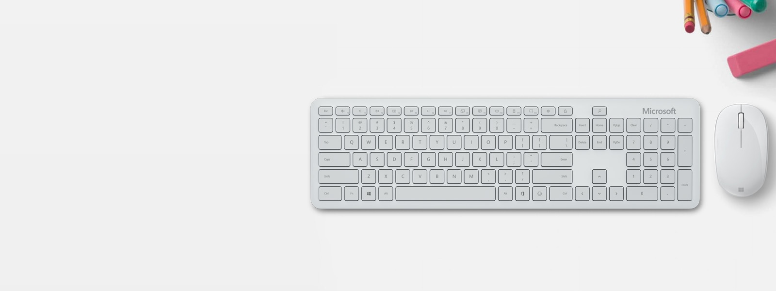 Microsoft Bluetooth Keyboard е поставена до Microsoft Bluetooth Mouse на бюро с писалка, маркер и гума