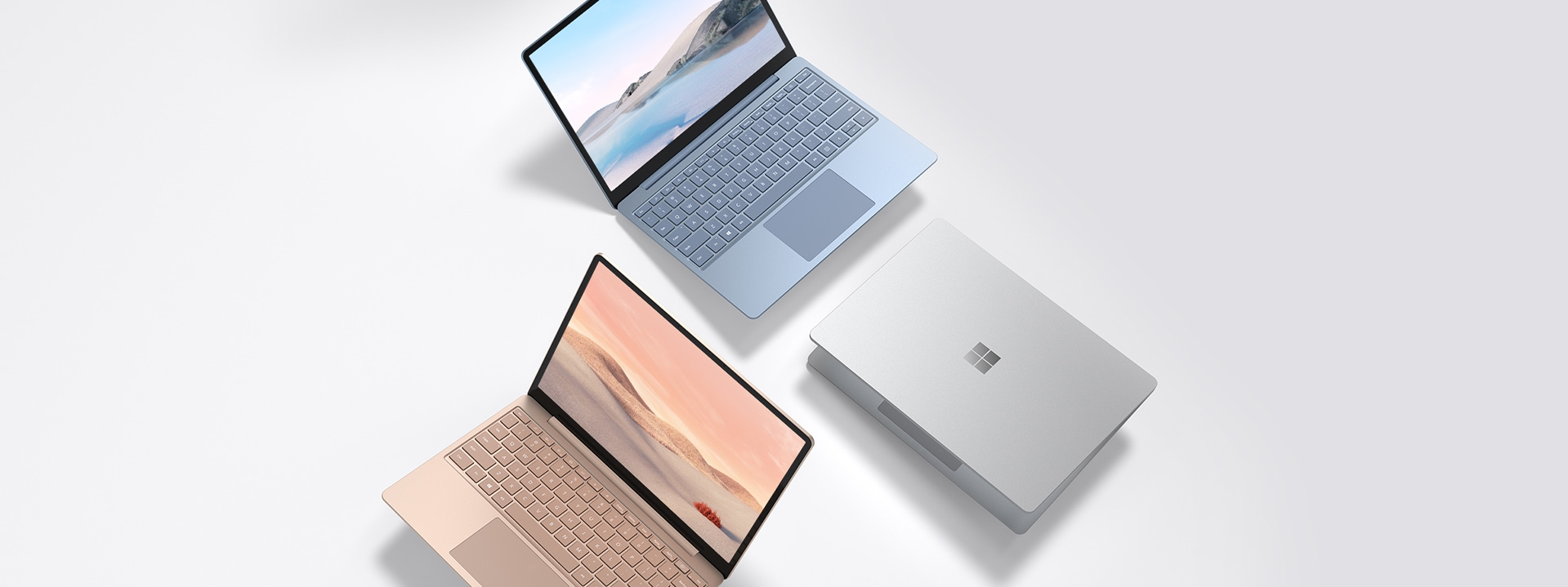 A series of Surface Laptop Go in sandstone, platinum and ice blue