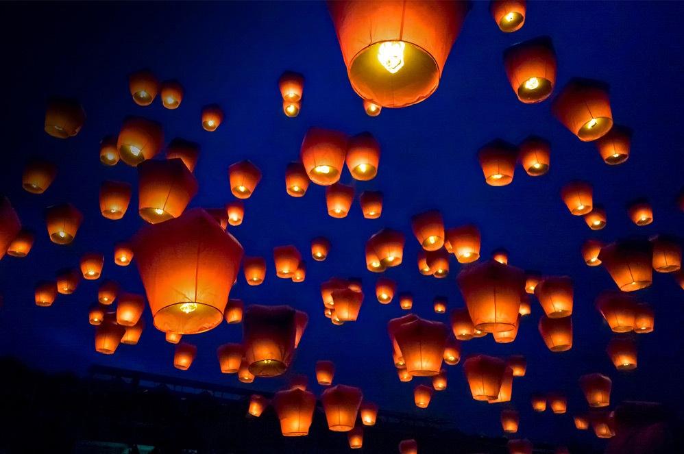 Orange paper lanterns float in night sky