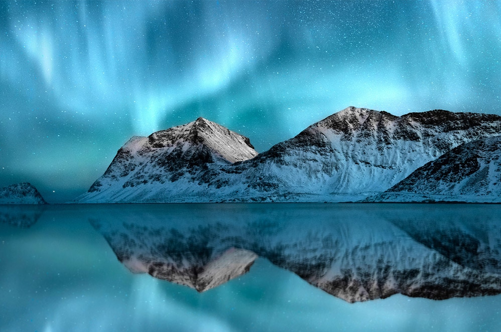 Northern lights over mountains reflect off water