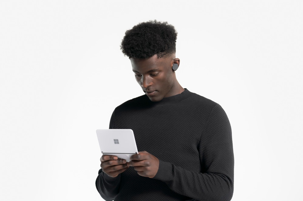 A person wears Surface Earbuds while typing on Surface Duo