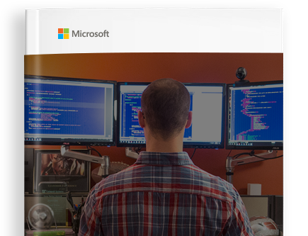 Image of a book cover with the Microsoft logo and a photo of a person working at a desk, looking at three desktop monitors.