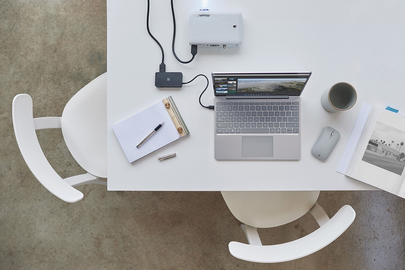 Surface Laptop Go على مكتب ومتصل بجهاز بروجيكتور