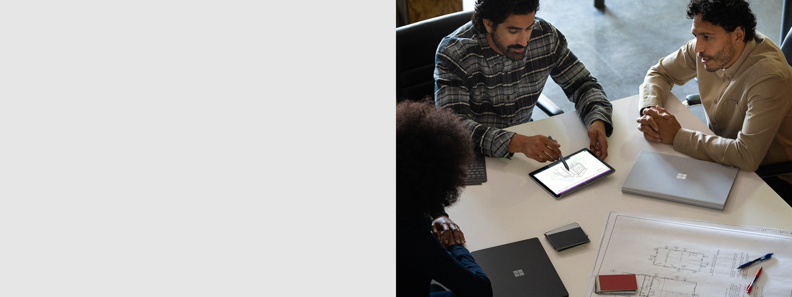 Commercial contextual image of a group of co-workers collaborating on Surface Go 2 in OneNote along with Surface Book 3 and Surface Pro X