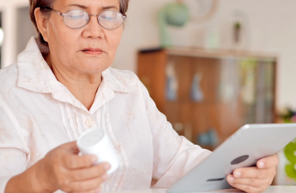 Older adult looking at a bottle of medication and holding a tablet device.