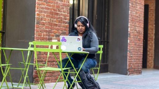 一位女士坐在咖啡桌旁写代码