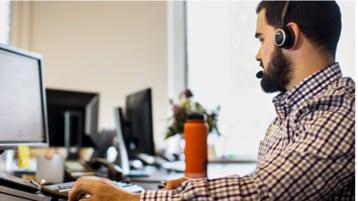 Mężczyzna z zestawem słuchawkowym pracuje na komputerze