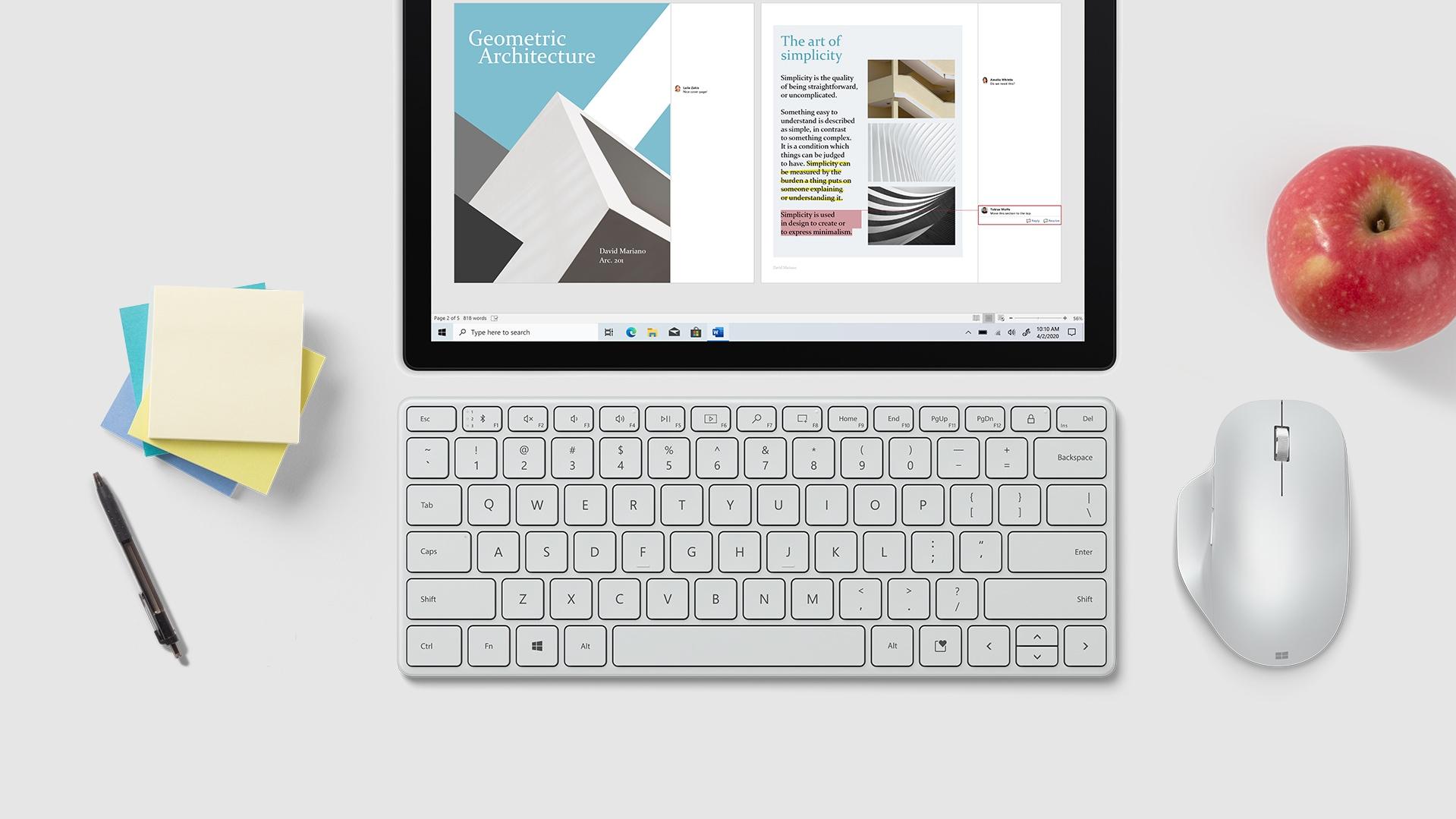 Microsoft マウス、紙、ペンの横ある Microsoft Designer Compact Keyboard。