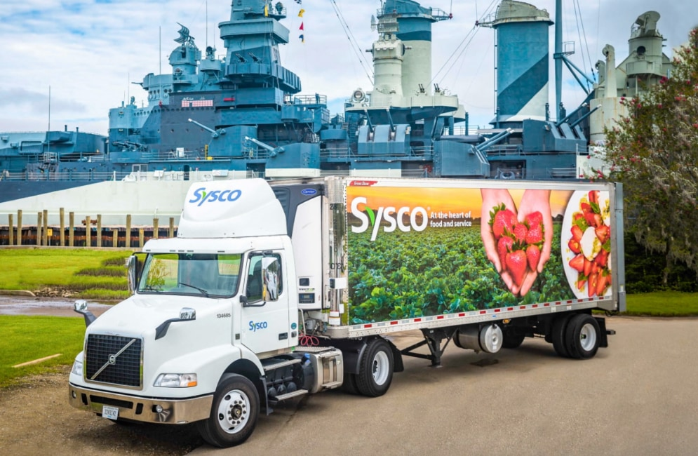 Sysco truck parked next to a large ship.