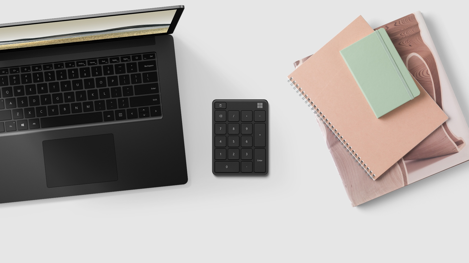 A Microsoft Number Pad next to a computer and day planner.