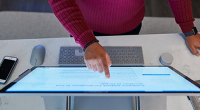 Человек стоит за столом и смотрит на экран компьютера