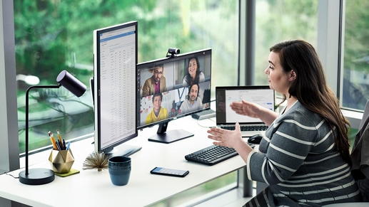 A person participating in a video call with 4 other individuals at their desk with multiple screens
