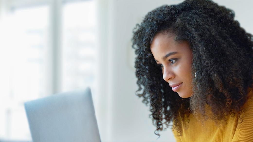 Woman using laptop to edit her résumé.