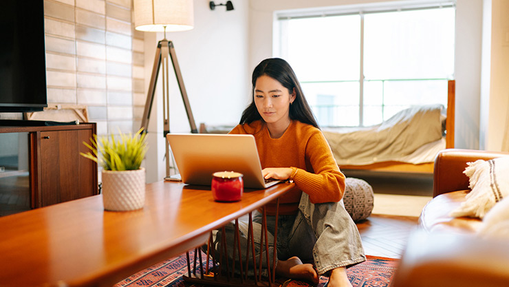 Woman sitting at coffee table on living room floor using Windows 10 laptop