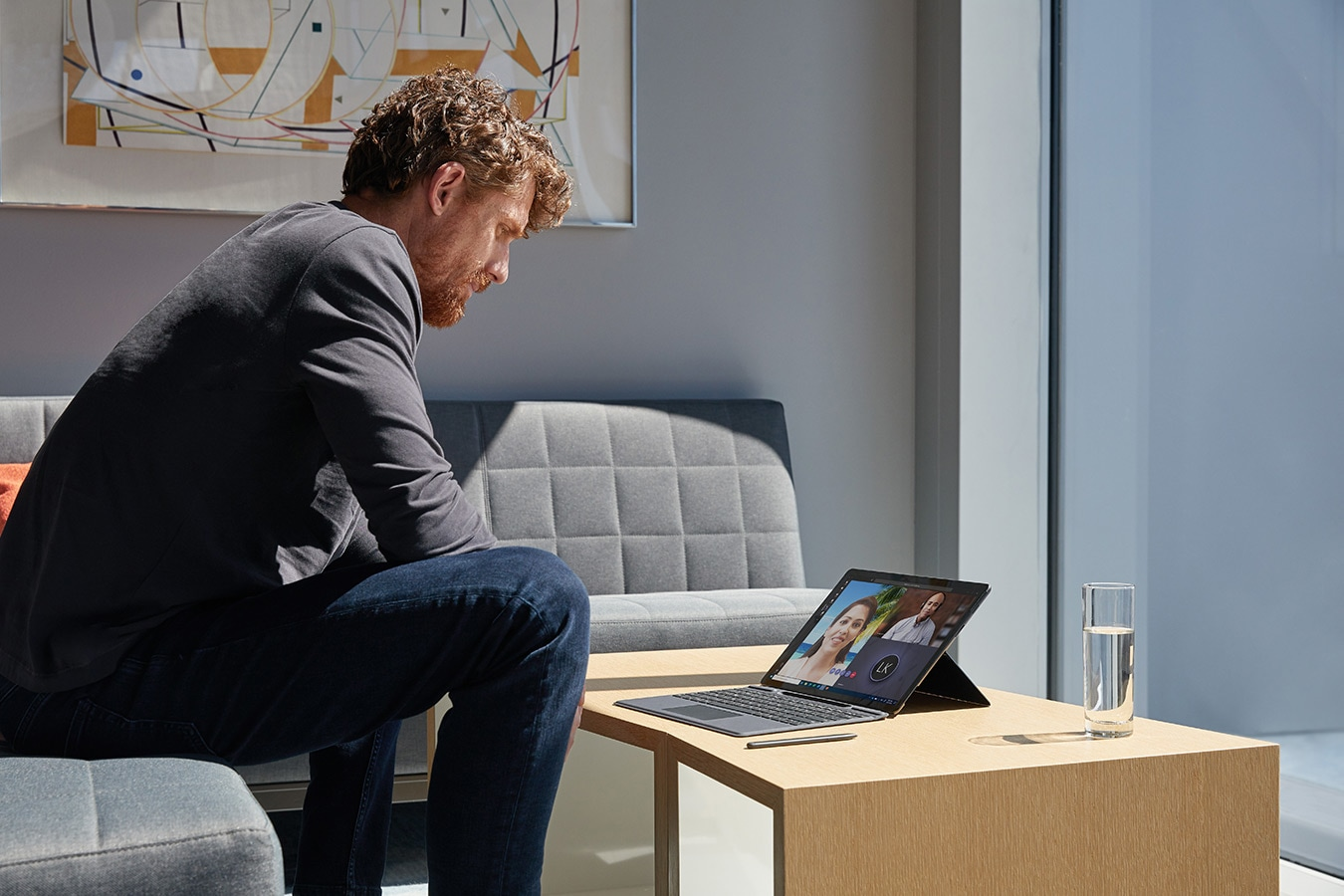 A person works on Surface Pro X while sitting on a sofa