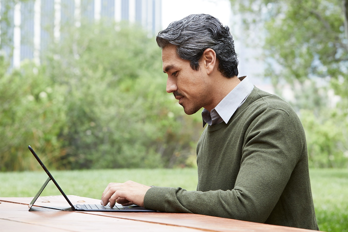 A person works on Surface Pro X while sitting outside
