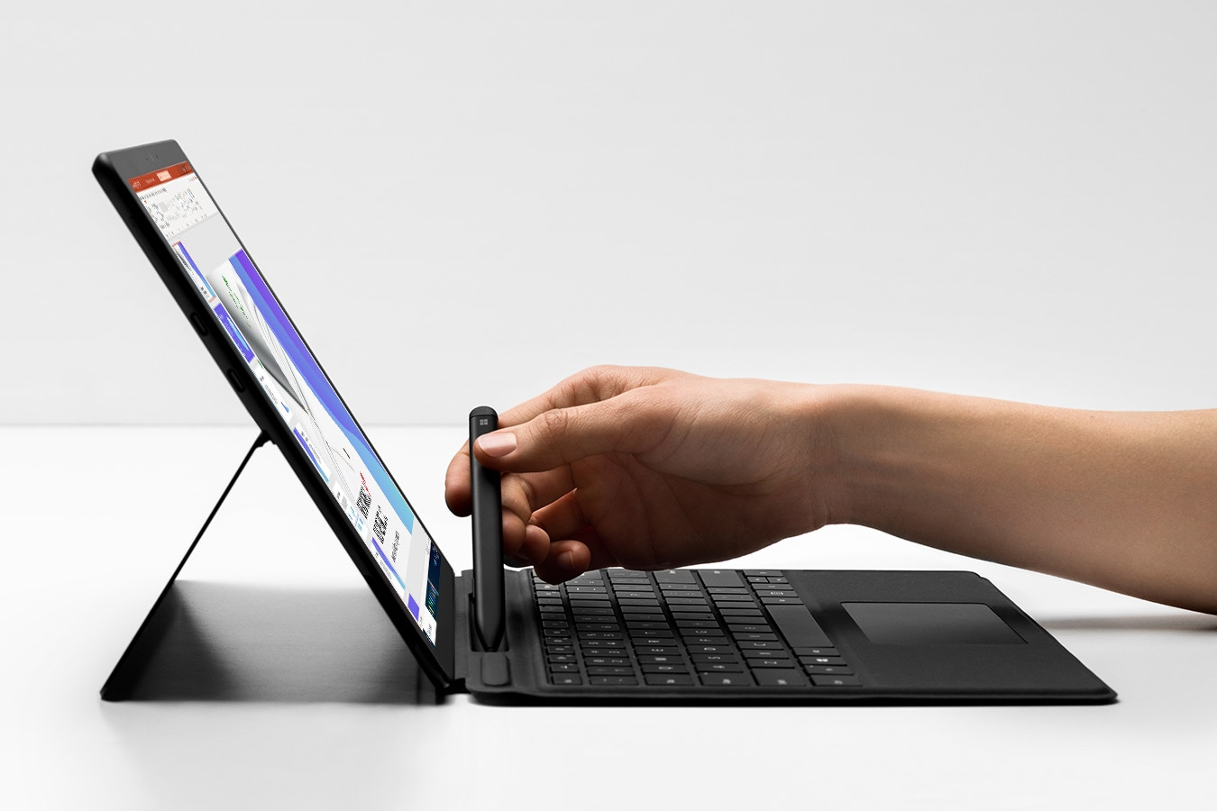 Eine Person hebt den Surface Slim Pen aus dem Ladebereich des Surface Pro X Signature Keyboard