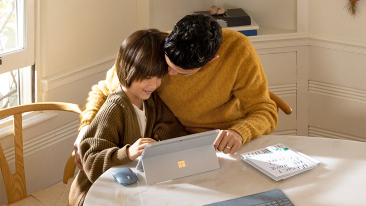 A father and daughter sitting at a round table working together on a Windows 10 PC