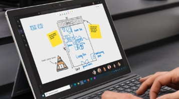 View of someone's hands using a Surface Pro in laptop mode with a floorplan on a virtual whiteboard in Microsoft Teams visible on the screen.
