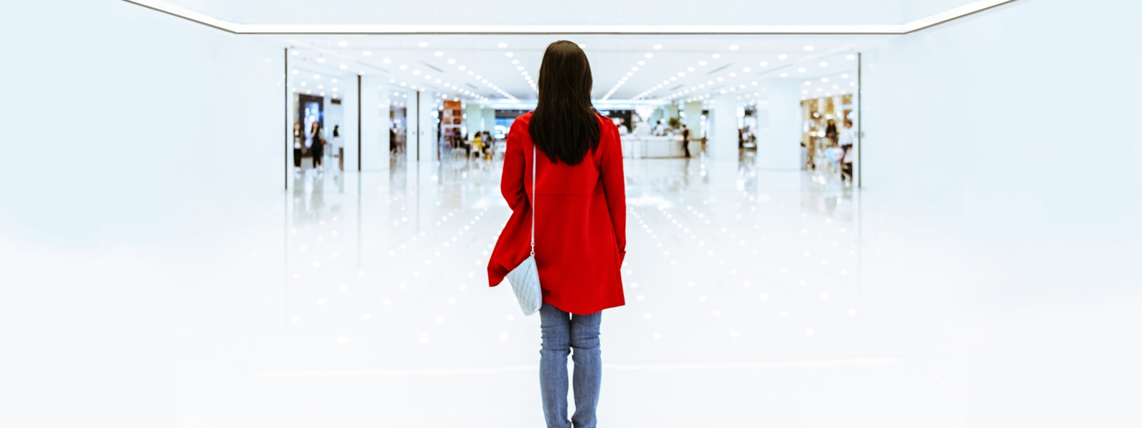 Person in a red coat standing in front of a retail store
