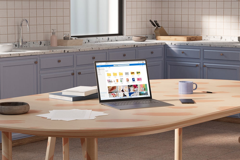 A tablet displaying Microsoft OneDrive sits next to a notepad, lamp, and dish with paperclips.