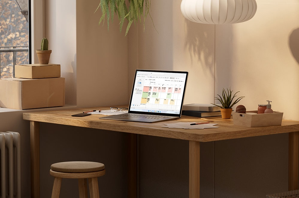 A phone and a tablet displaying Microsoft Outlook sit next to a fan, paper, and a pen.