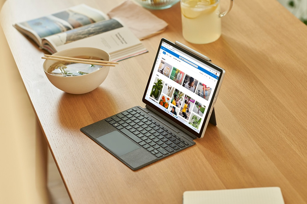 A tablet displaying Microsoft Word sits next to a plant, a water bottle, and an ID card.