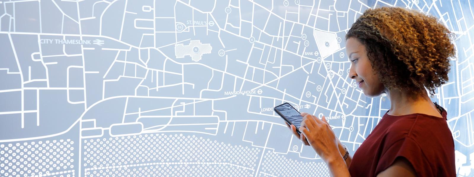 Eine Frau nutzt ein mobiles Gerät vor einem Stadtplan.