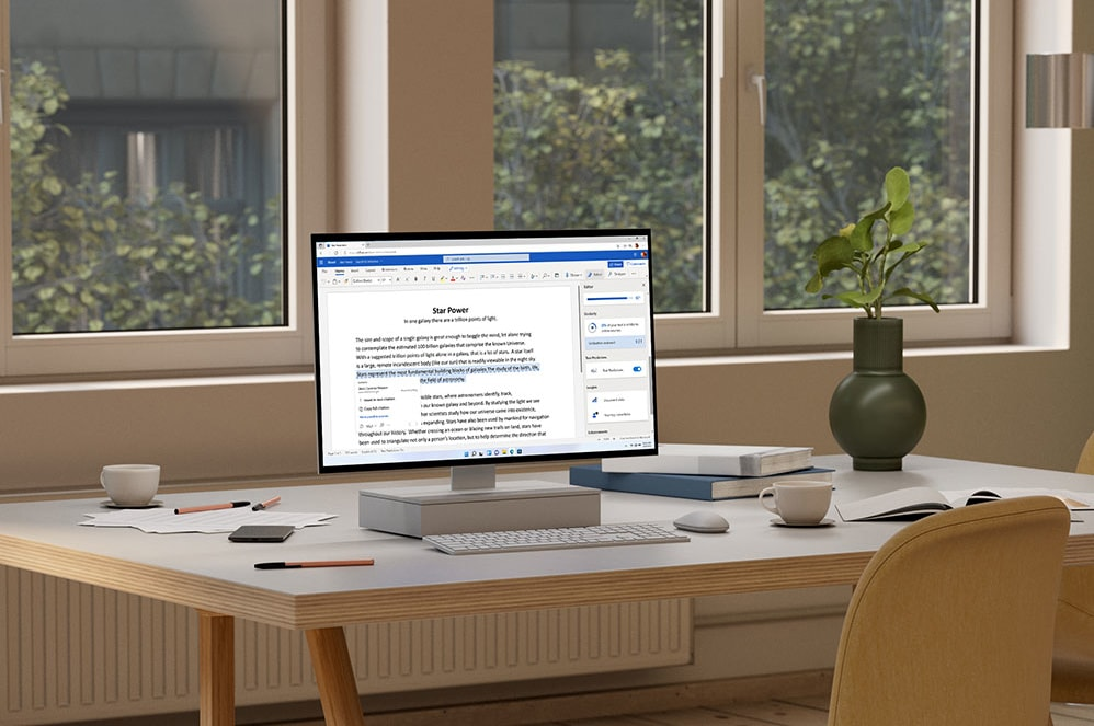 A tablet displaying Microsoft PowerPoint sits next to a camera, cup of coffee, and rolls of paper.