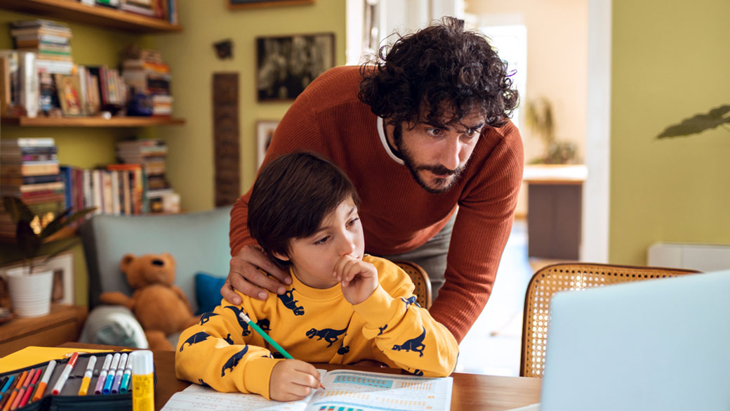 Photo credit: Marko Geber/DigitalVision/Getty Images. Father helping son with schoolwork at home