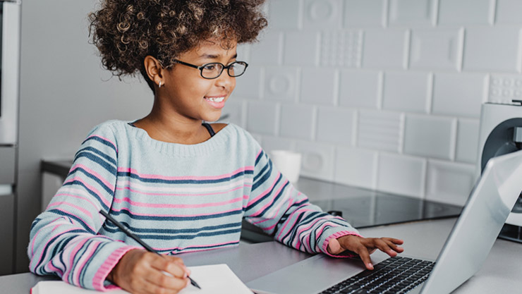 A young woman sitting at her desk with one hand writing on a piece of paper and the other hand typing the keyboard on her Windows 10 PC