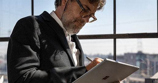 Person wearing glasses using a pen and tablet device.