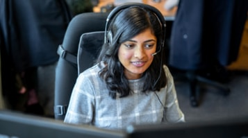 A person wearing a headset, looking at a set of large desktop monitors.