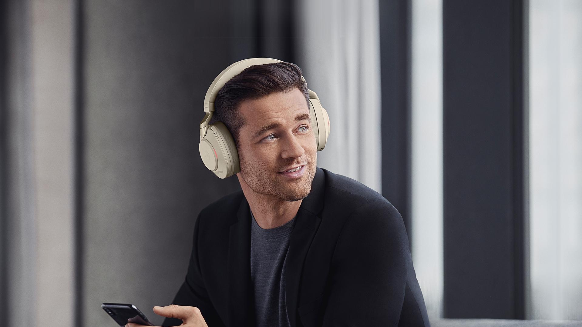 Un homme avec une paire d'écouteurs Jabra Evolve2 85 beige