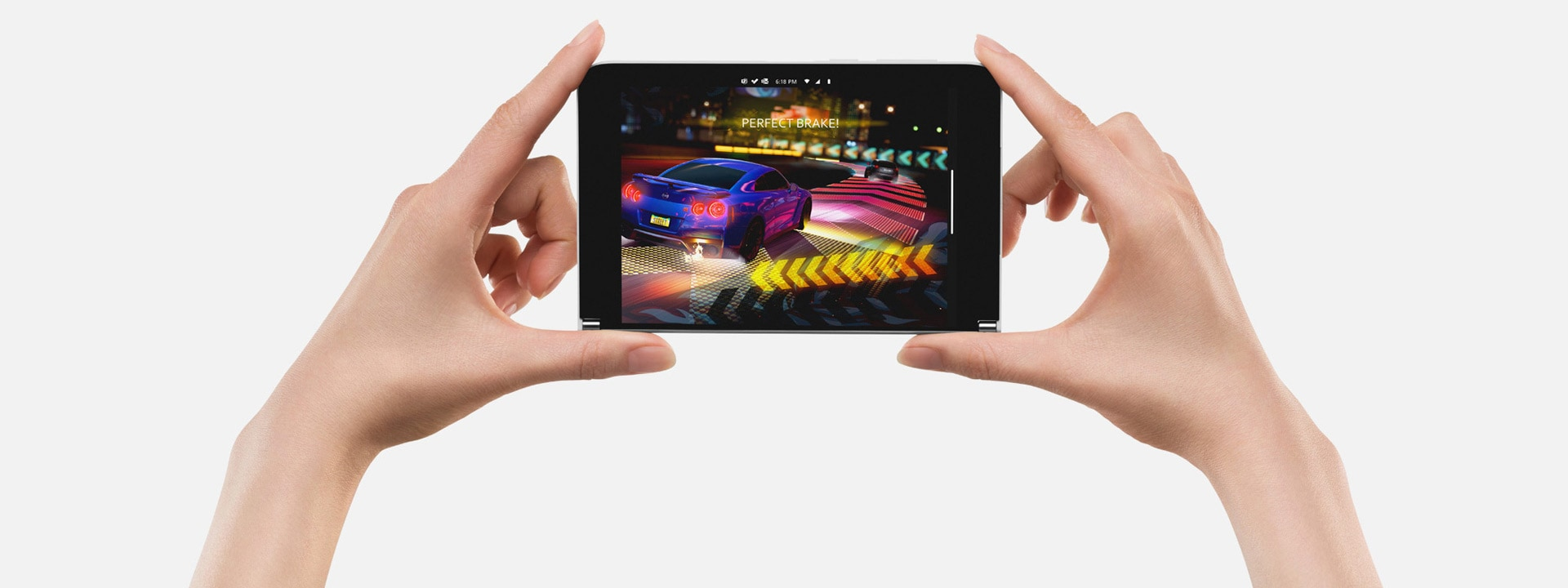A pair of hands holding Surface Duo, on the screen is Forza, a car racing game
