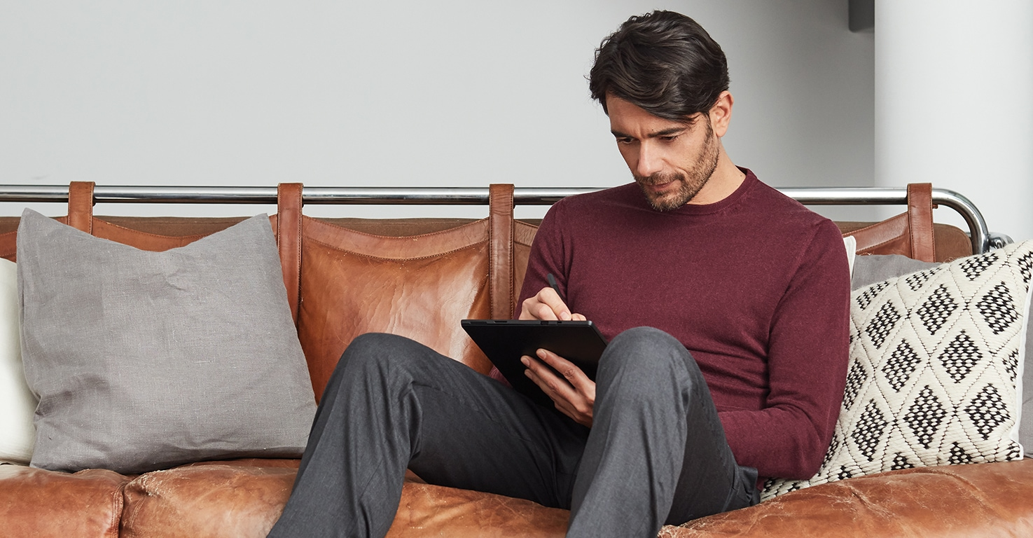 A man is sitting on a couch and using a tablet.