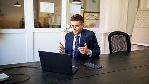 Un uomo in un ufficio lavora con un computer desktop.