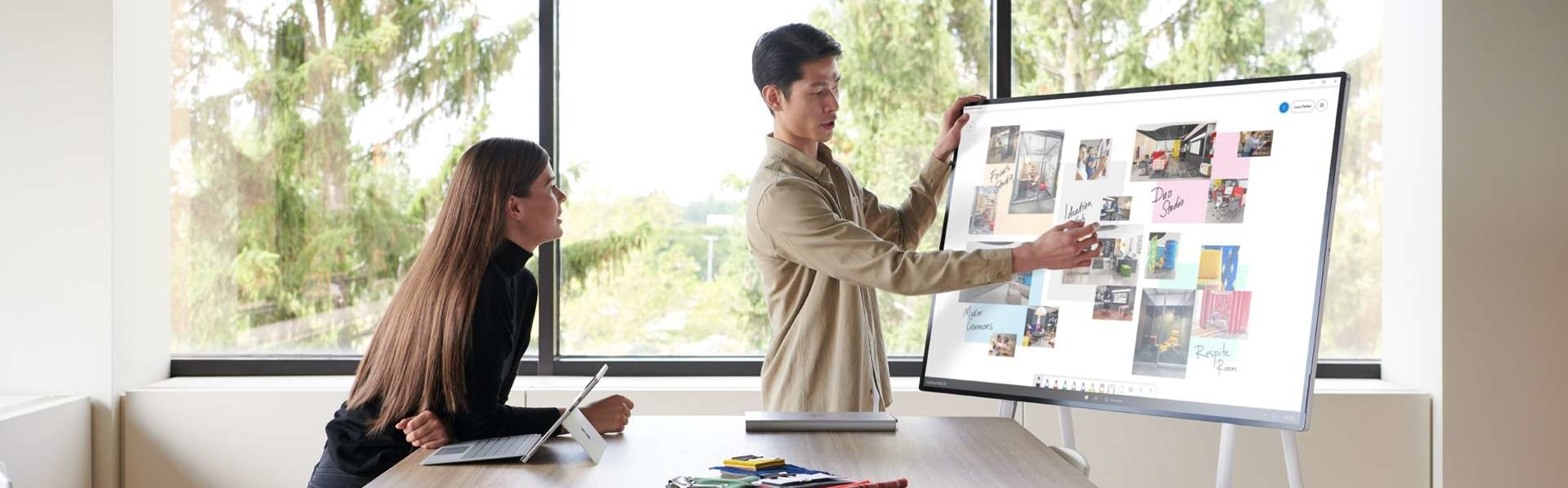 Two team members whiteboard ideas with Surface Hub 2S in an open office setting