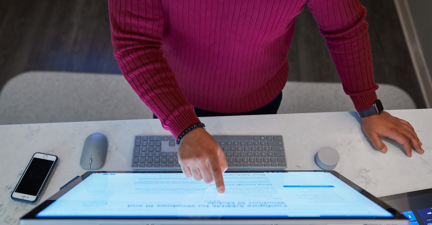 Person using a touchscreen desktop device.