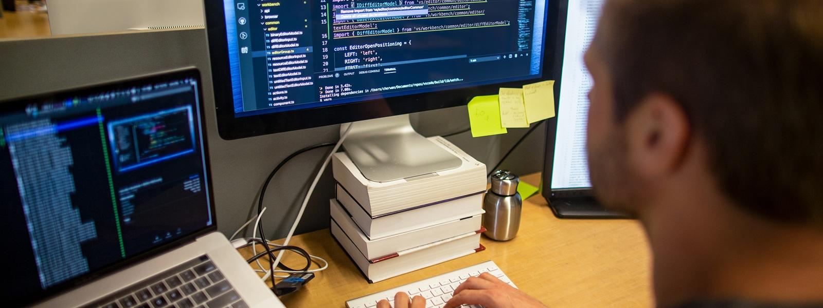 Osoba, která u svého pracovního stolu používá laptop a stolní monitor