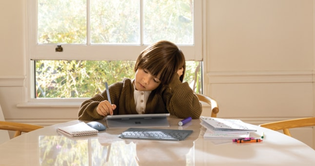 A child sitting at a table using a tablet with a pen. There is a wireless mouse and keyboard, and various school supplies around them.