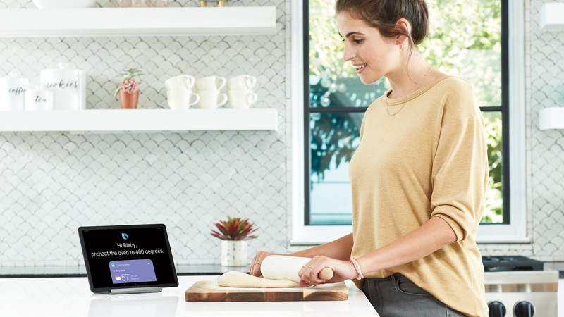 A woman using the Samsung Galaxy Tab S5e in her kitchen while baking