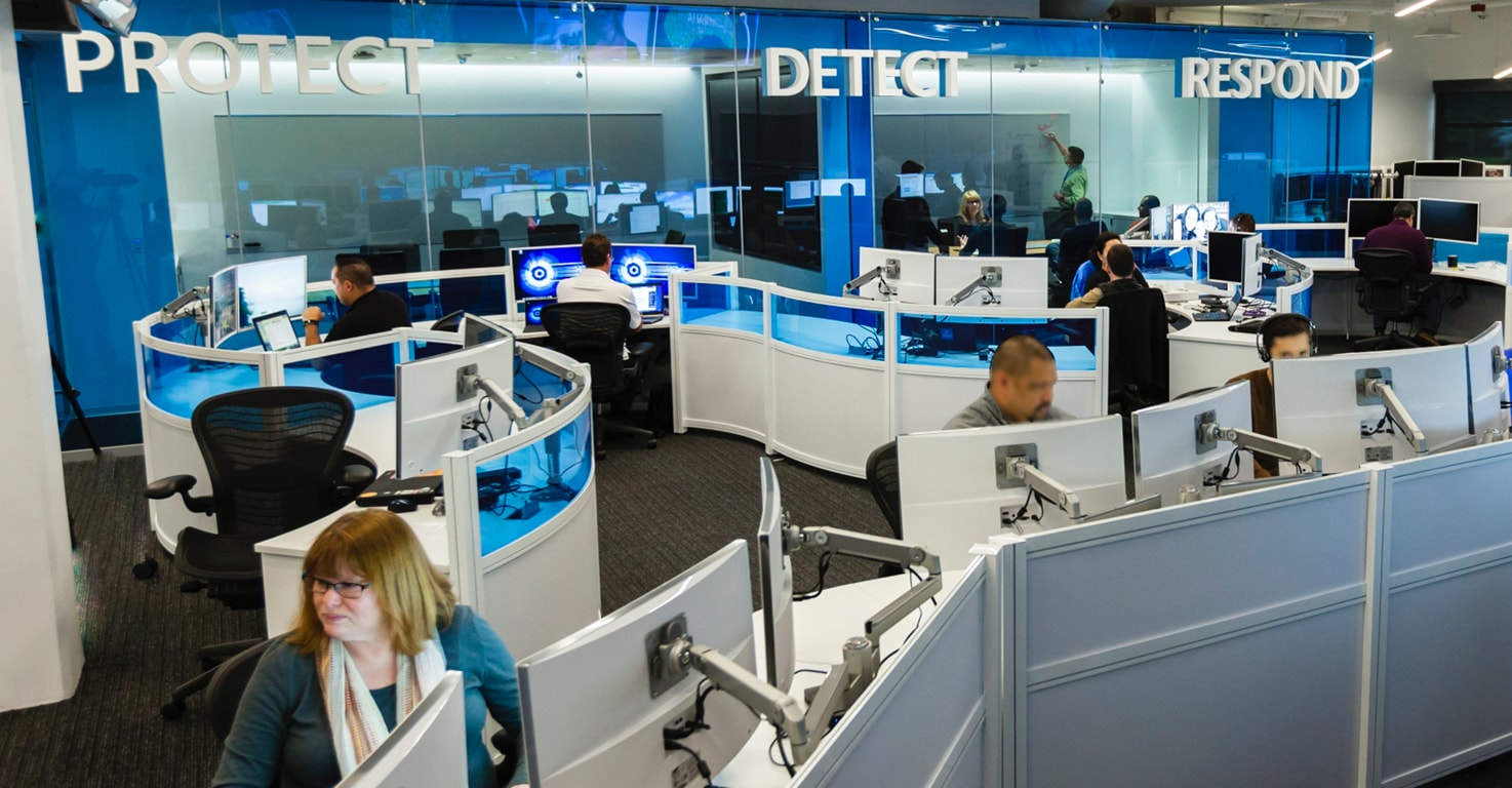 An office with blue glass dividers between desks and the words Protect, Detect and Respond on the walls.