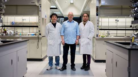 Three people smiling at the camera in a lab environment.