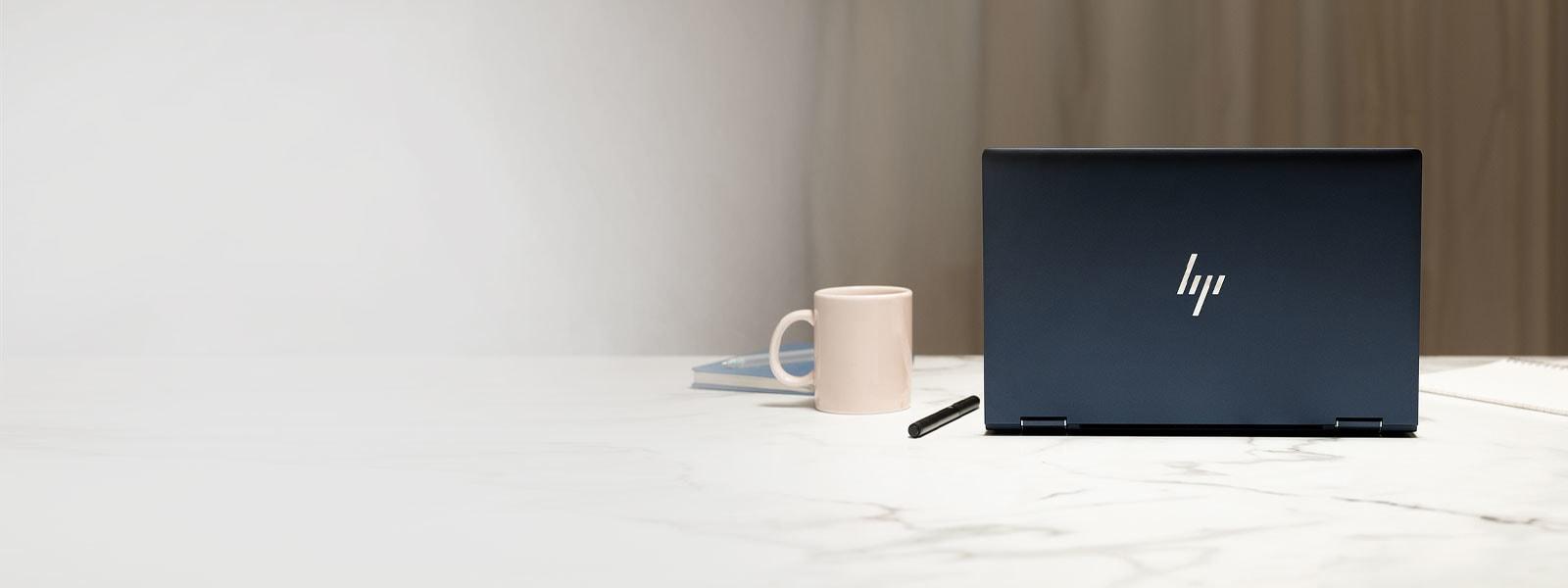Un portatile HP Elite Dragonfly su un banco, tra una tazza e un blocco per appunti