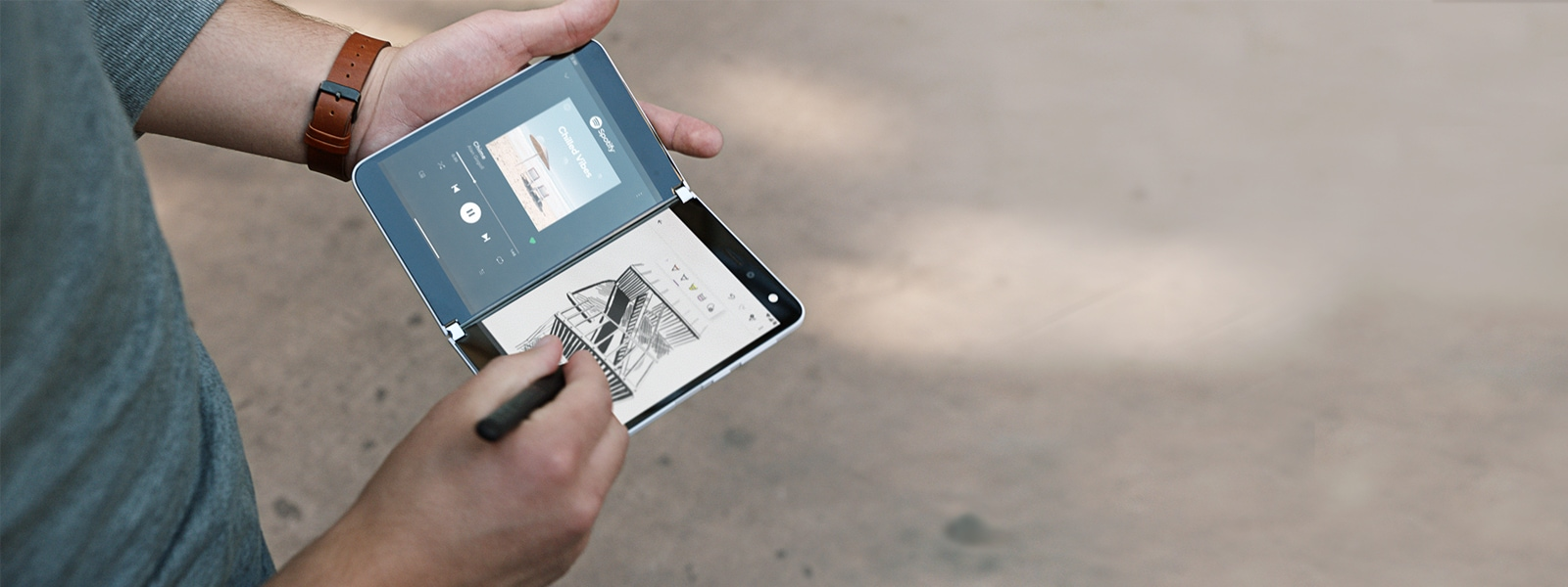 Surface Duo being used with a Surface Pen to sketch out an architectural drawing on one screen and having music play on the other screen.