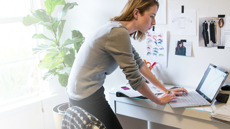 Woman designs clothing in her home office, standing over her desk using a Windows 10 laptop.