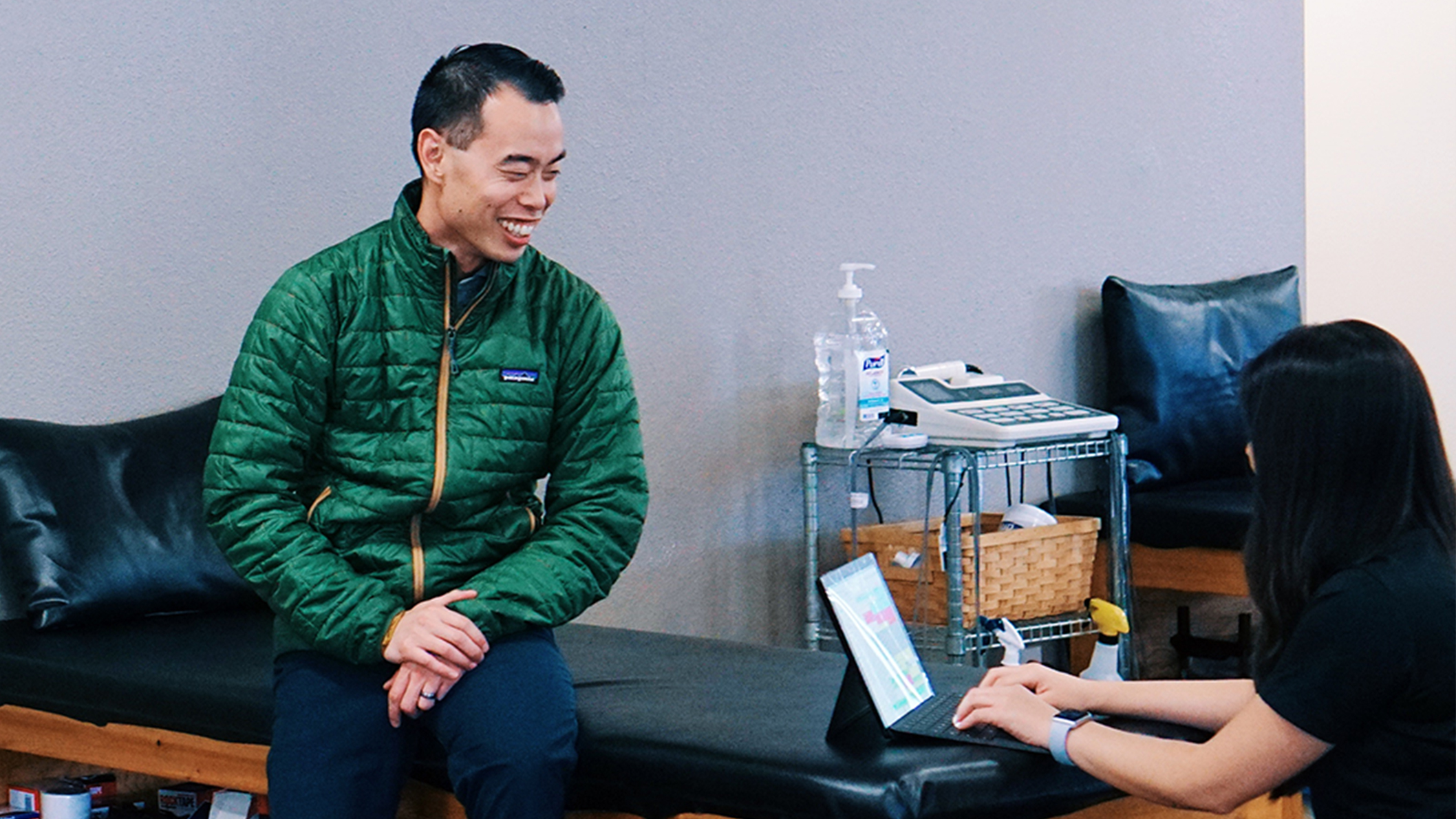 A physical therapist uses a Surface device to take notes while talking to a patient.