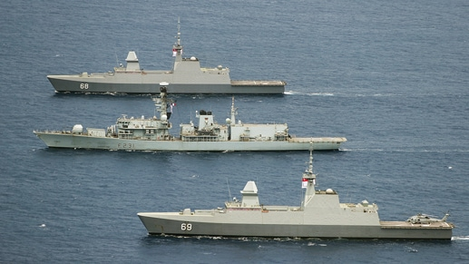 An image of three military ships in the ocean.