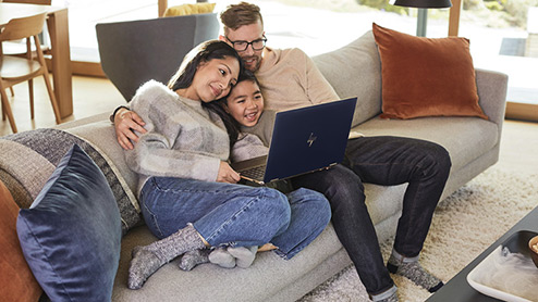 Dad, daughter and son smiling at open Windows 10 laptop on couch